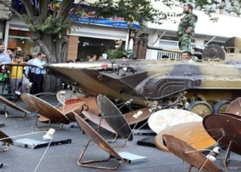 قوات الأمن الإيرانية تجمع أطباق الأقمار الصناعية وتحطمها بالدبابات لأغراض دعائية.